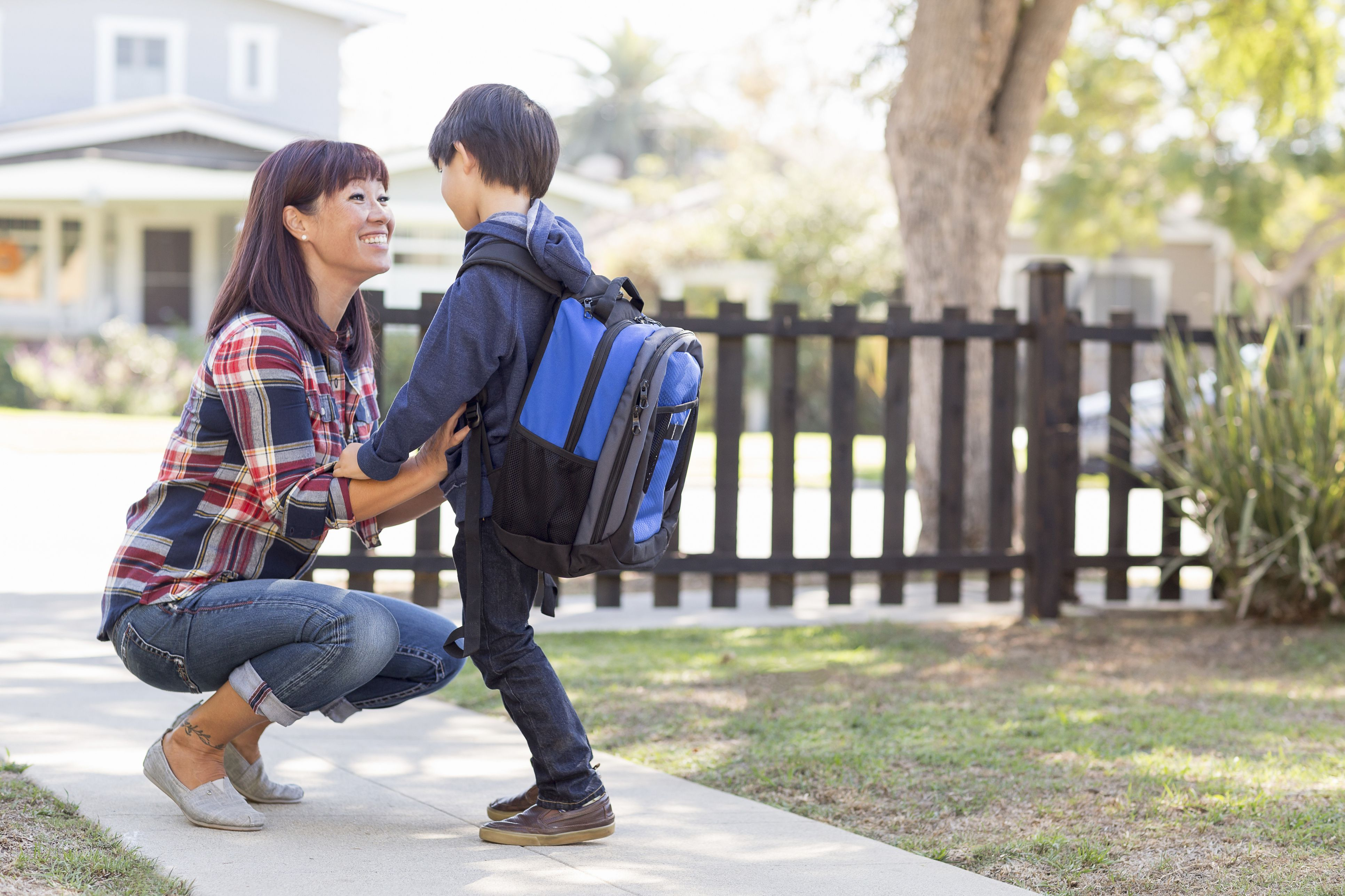 Mother crouching down to talk to young boy on sidewalk