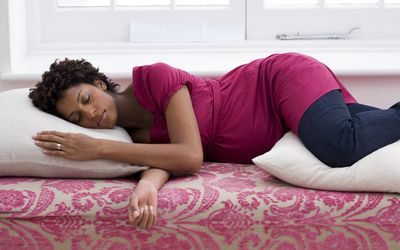 Pregnant woman sleeping on bed