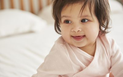 Close up of happy baby girl sitting up on bed
