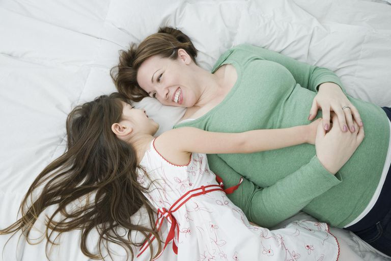 Mother and daughter (4-5) lying on bed, laughing and looking at each other.