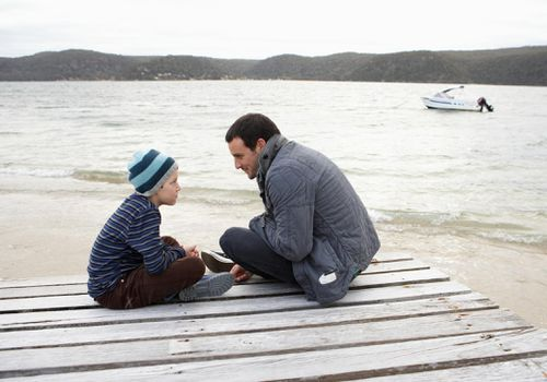 Father and young son sitting on a dock near a lake and looking at each other