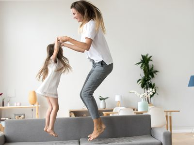mom and daughter jumping on couch