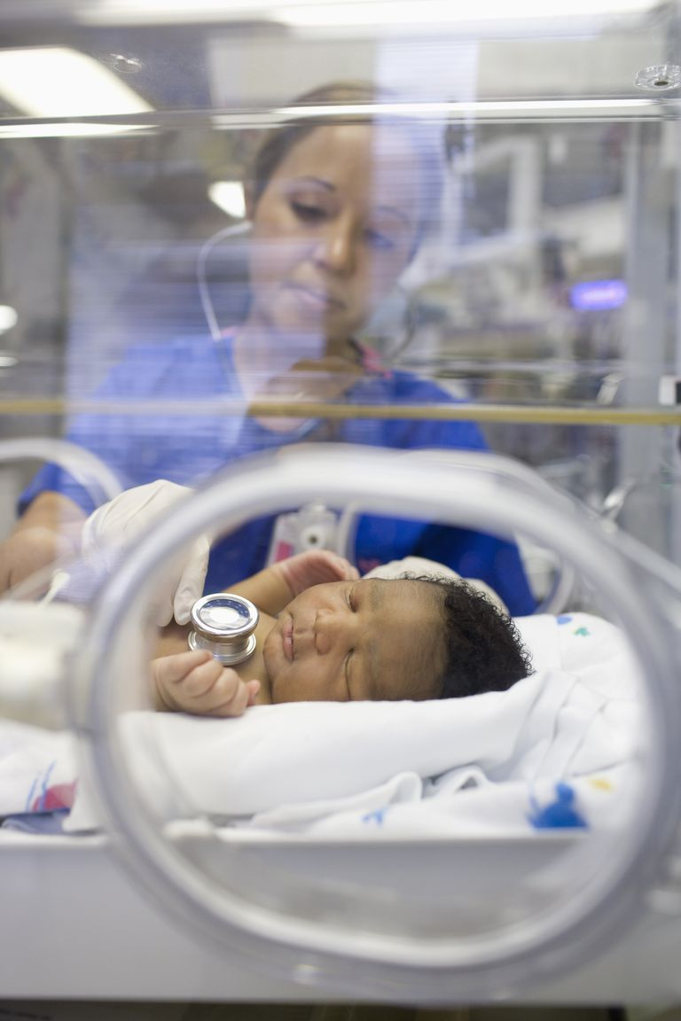 Nurse listening to baby's heartbeat in hospital