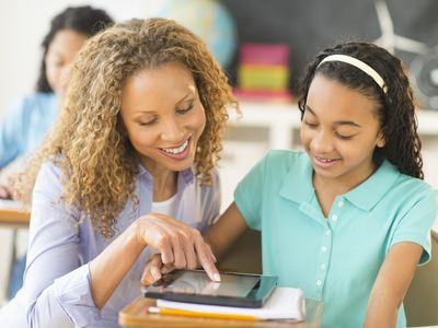 USA, New Jersey, Jersey City, Schoolgirls (10-13) using tablet pc, assisted by teacher