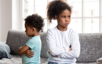 An angry brother and sister facing away from each other with arms crossed