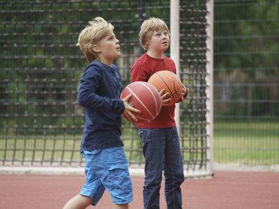 Boys holding basketballs while looking up at court