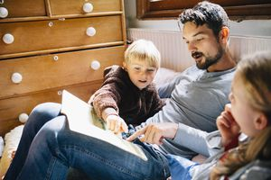 young boy reading with father