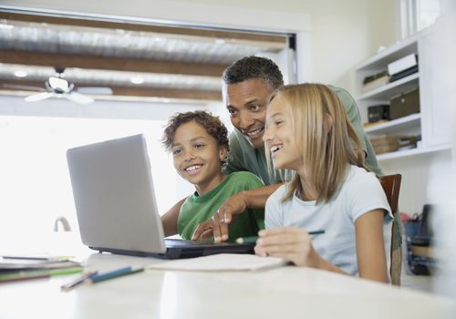 father and two kids looking at laptop