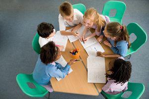 Elementary school children sitting around table, having discussion