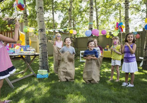 Kids enjoying sack race at backyard birthday party