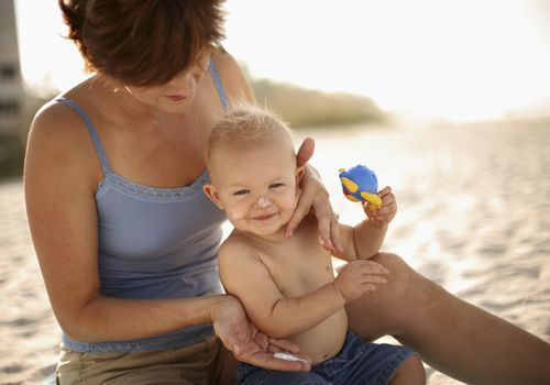 Mother putting sunscreen on baby at the beach