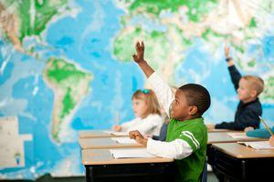 kids raising hands in a first grade classroom