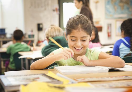 second grade girl in classroom smiling