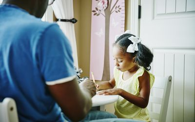 Girl writing while dad watches.