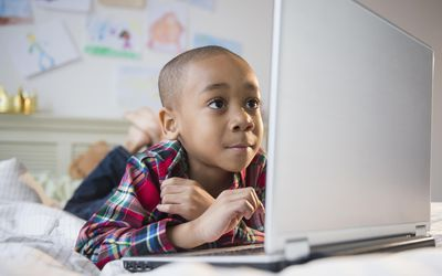 boy using laptop on a bed