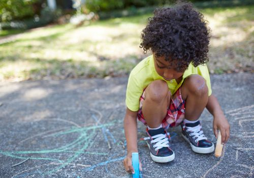 Young boy using sidewalk chalk