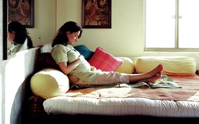 Pregnant woman lying on futon, looking at abdomen, side view