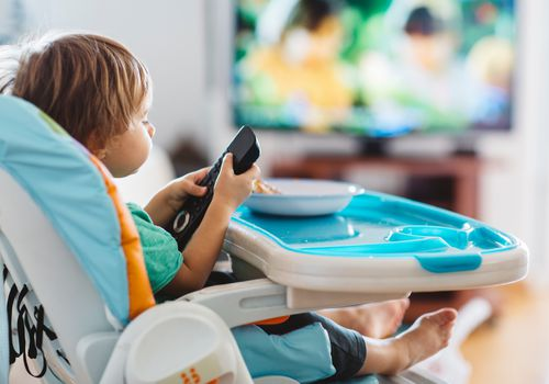 Toddler in high chair with tv in background