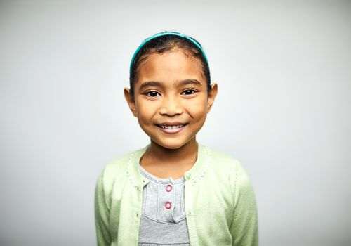 Young girl in green sweater smiling at the camera
