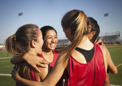 Female teens on a soccer field hugging