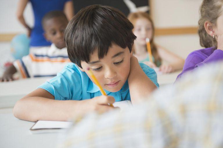 School children (8-9) learning in classroom.