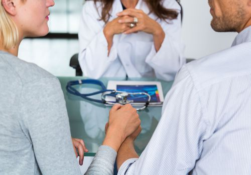 Doctor discussing with a couple during consultation.