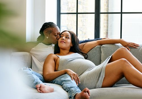 Pregnant lesbian couple relaxing on sofa
