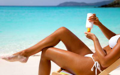 woman in bikini applying sunscreen lotion at a tropical beach