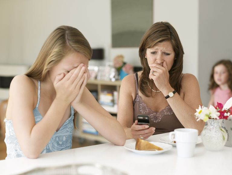 shocked mother looking at upset daughter's cell phone