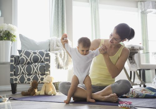Mother playing with baby girl on exercise mat at home