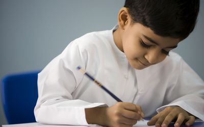 A small boy doing his class work in a classroom.