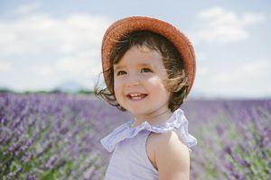 Little girl wearing a hat in a field of purple flowers