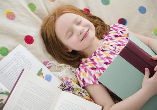 smiling young girl in bed with her eyes closed and an open book on her chest
