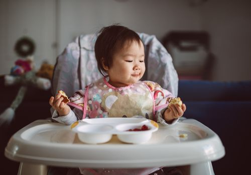 Lovely little baby enjoying breakfast by herself