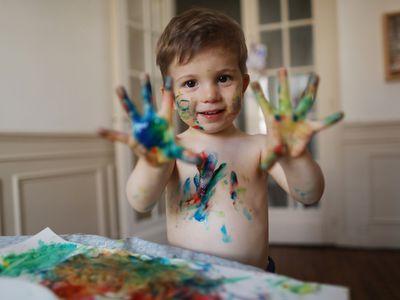 little boy using finger paints