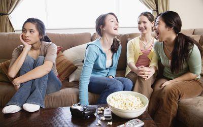 Teenage girls (14-15) on sofa,three girls talking,one looking away
