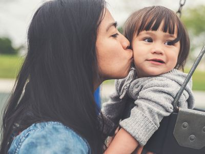 Mom kissing toddler who is sitting in a swing