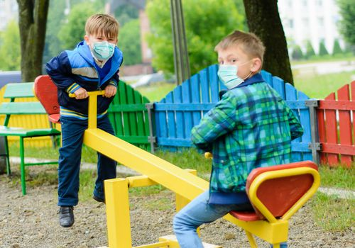 two boys playing outside with masks on