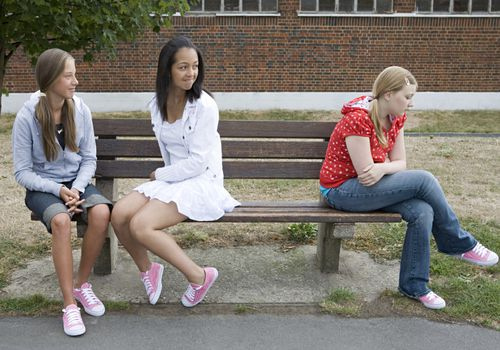 Teen girl sitting on a bench, turned away from two other teen girls who look at her