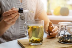 Woman dropping CBD oil into tea