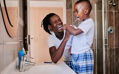 dad teaching son to brush teeth