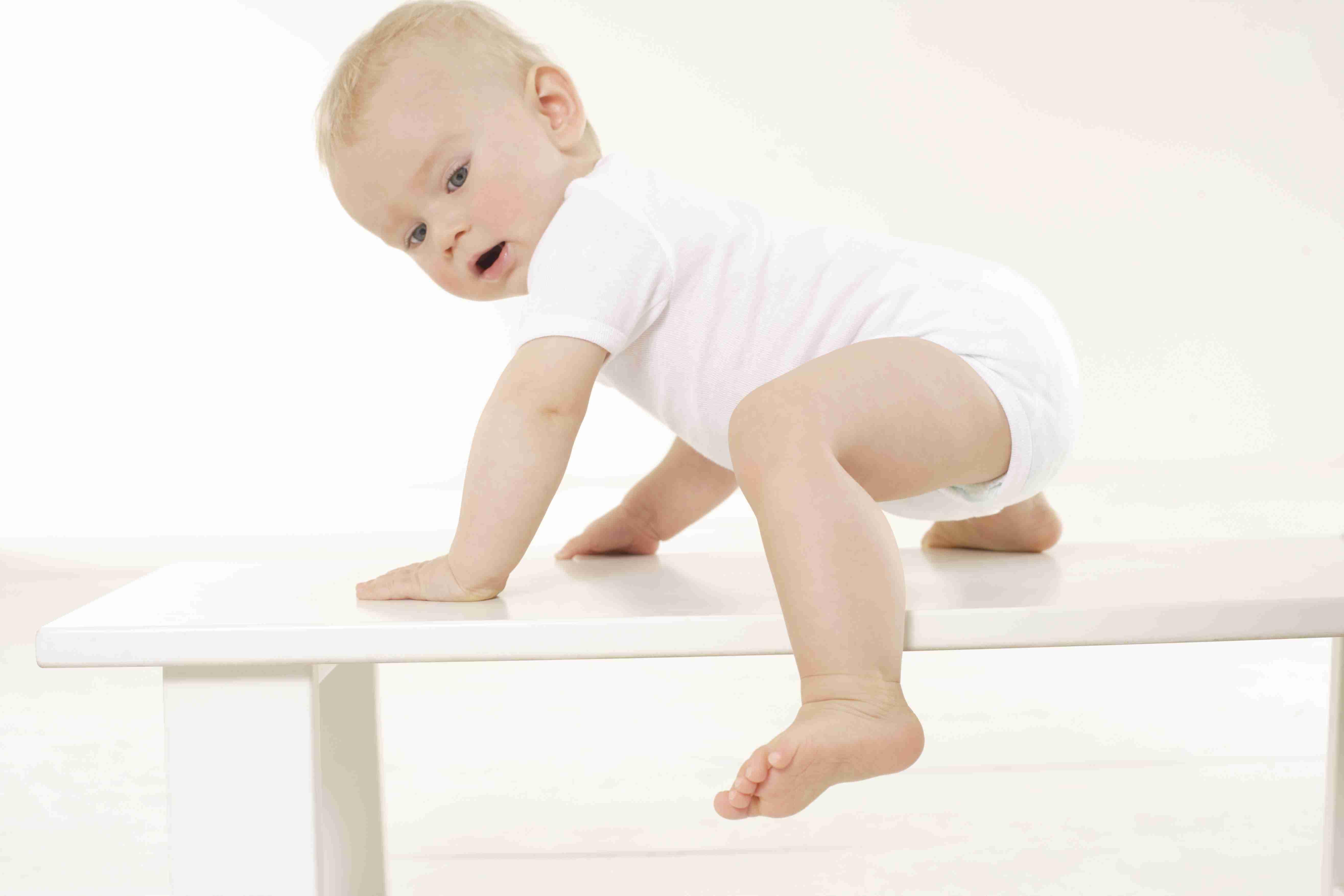 Baby climbing on furniture.