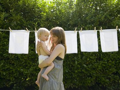 mother and baby in front of diapers on clothesline