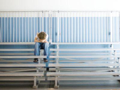 Boy upset in bleachers at school