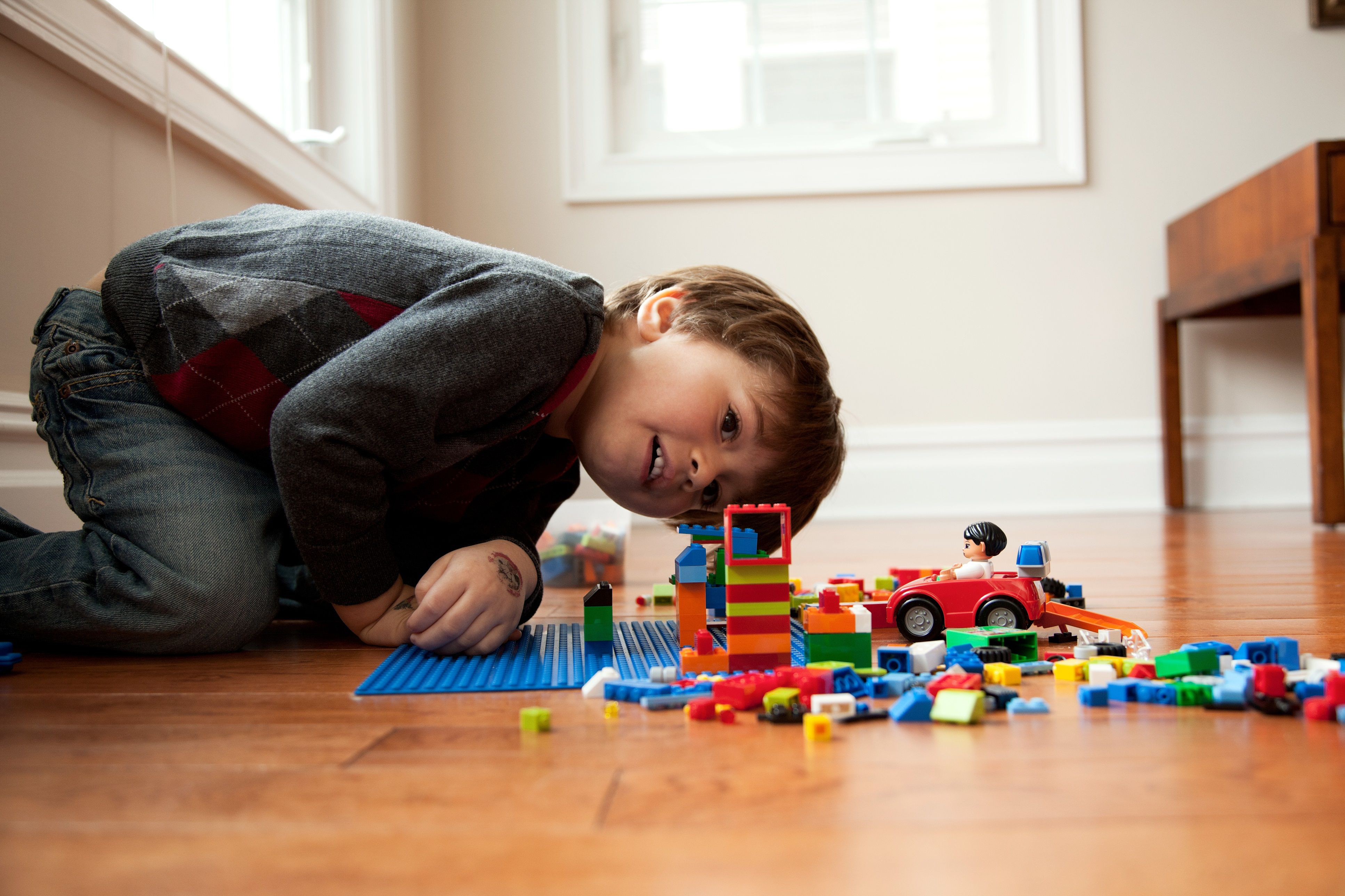 pretend play - boy on floor with Lego
