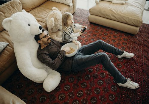 Father and daughter sitting on teddy bears watching TV