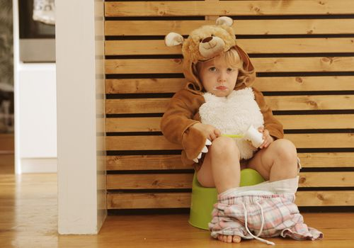 Toddler eating yogurt while sat on a potty dressed as a bear