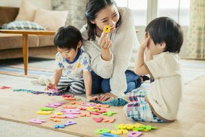 A picture of a mom playing with letters with her kids