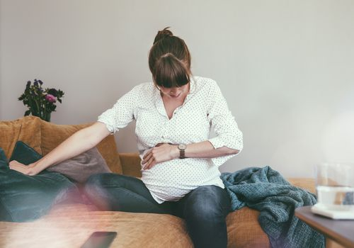 pregnant woman holding her belly on the couch