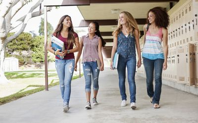 Four teen girls walking together at school